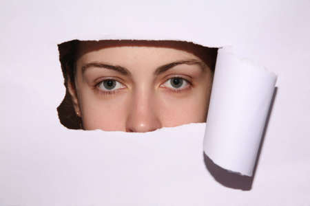 woman looks in the hole of the sheet of paper Stock Photo - 3030522