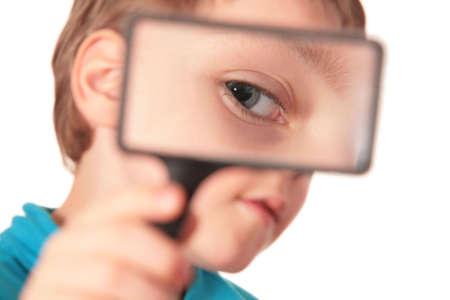 child looks through magnifier photo