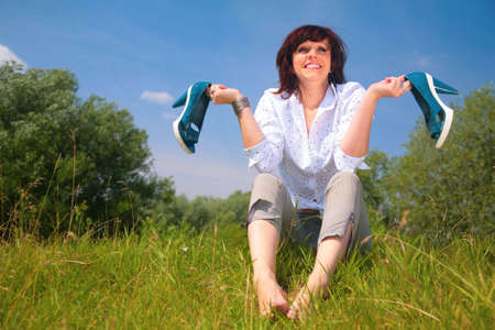 woman sits on grass and holds shoes in hands photo