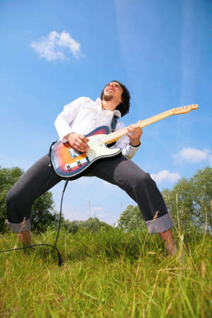 young man plays on guitar on grass photo