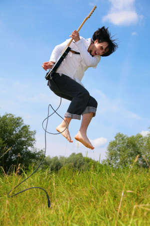 young man jumps with guitar on grass photo