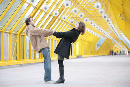 diagonals: boy and girl hold each other for  hands on  footbridge