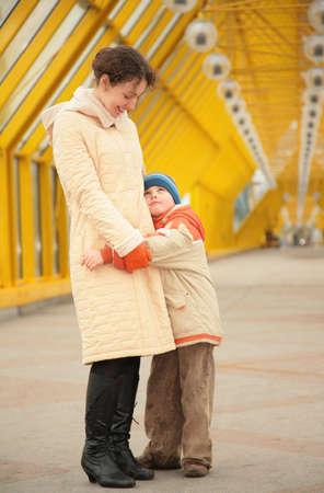 diagonals: son embraces mother on footbridge