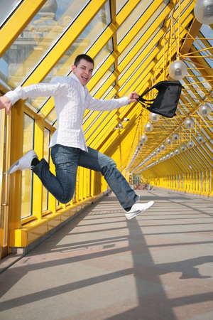 young man jumps with bag on footbridge photo