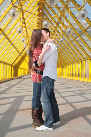 young pair kisses on footbridge photo