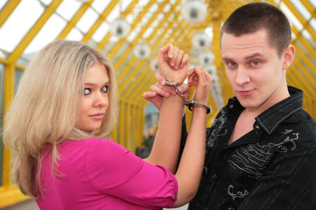 prisoner woman: young man and blonde in handcuff