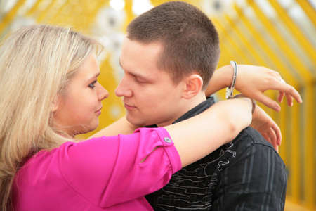 young man and blonde in handcuff look each other photo