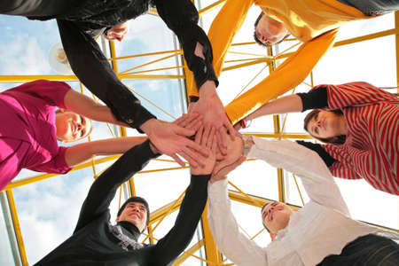 Six friends joining hands low angle view Stock Photo - 5134591