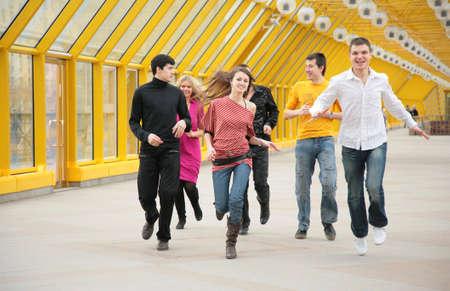 group of friends runs on footbridge