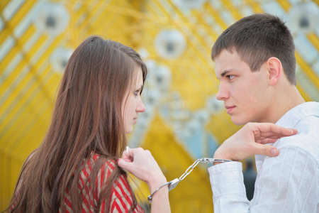 Young couple with handcuffs on footbridge photo