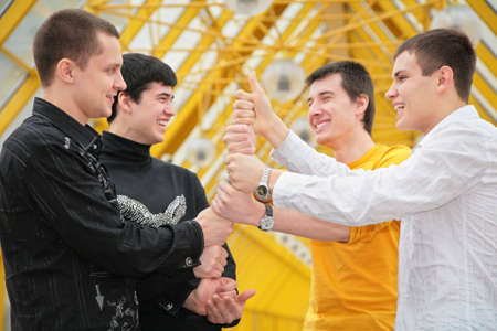 group of young men make piramid from hands photo