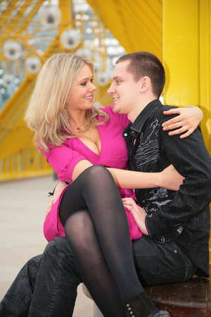 blonde sits on boy`s knees on yellow footbridge photo