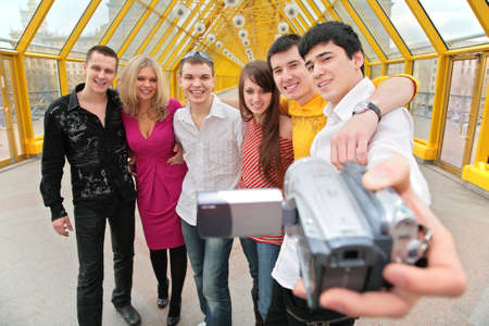 footbridge: group of young persons removes itself to video camera on footbridge Stock Photo