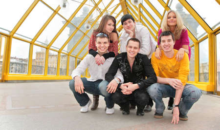 group of young people pose on footbridge photo