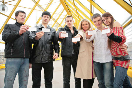 group of young people hold blank cards in hands . focus on cards photo