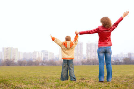 mother and son stand outdoor with lifted hands photo