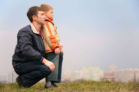 father and son on grass. city photo