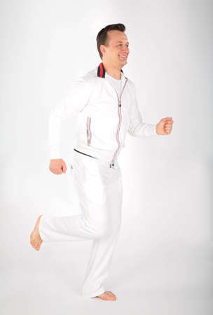 man in white sports suit runs barefoot photo