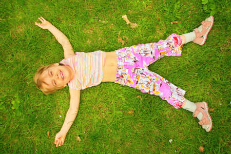 back ground: smiling little girl lies on back on grass