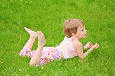 lying on the stomach: little girl lies on grass on belly Stock Photo