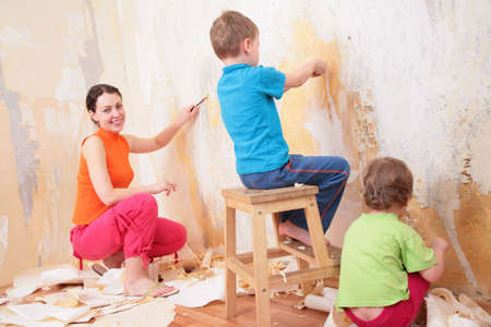 children help mother remove old wallpapers photo