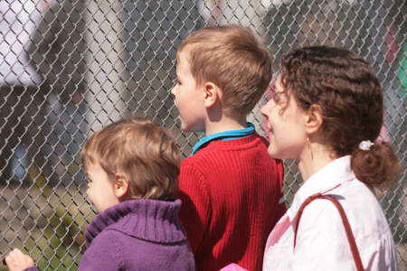 Mother and children look through lattice Stock Photo - 5138839