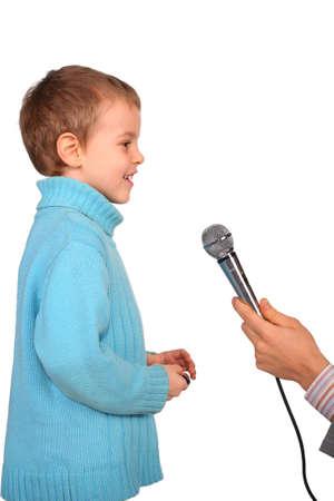 speaks: boy speaks into  microphone Stock Photo