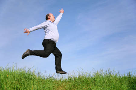 fat man jumps on meadow Stock Photo