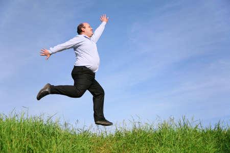 bald man: fat man jumps on meadow Stock Photo