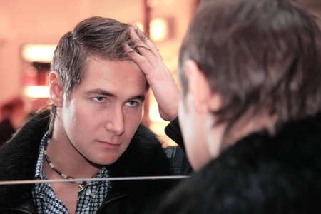 mirror face: young man looks in mirror