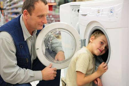 inward: Man looks at washing machine in store, boy glances inward it Stock Photo
