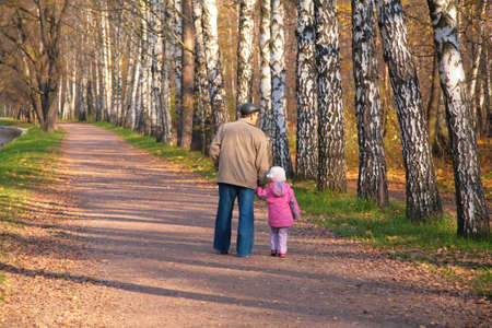 Grandfather with granddaughter walk in park in autumn  photo