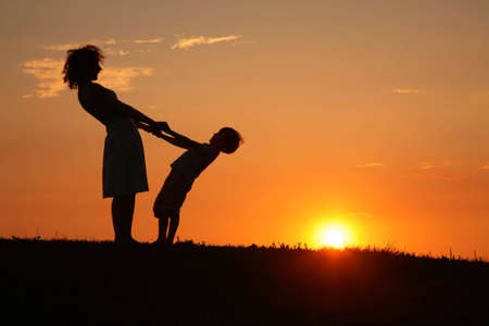 shadowgraph: Mother and son on sunset holding by hands