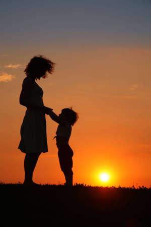 mama e hijo: Madre e hija en la puesta de sol silueta
