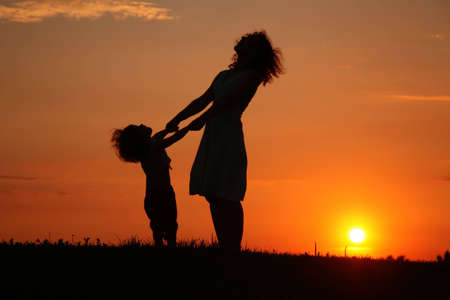 shadowgraph: Mother and daughter on sunset watching on sky