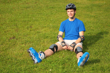 rollerskates: Guy in rollerblades sits on grass