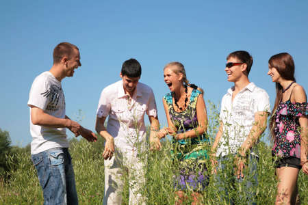 Group of five friends stands among grass Stock Photo - 5201483