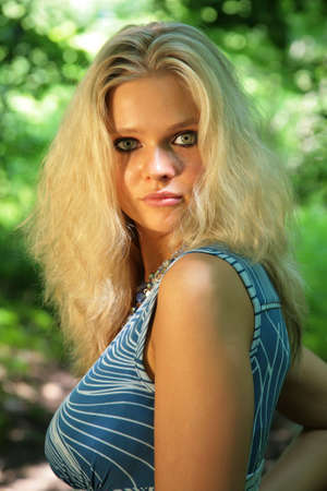 Young beautiful blonde with black eyes in dark in wood photo
