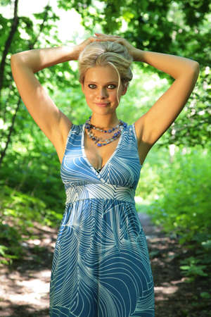 Young beautiful blonde in wood with rised hands photo