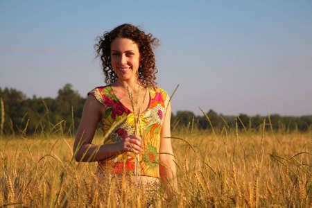 earns: Young woman with earns stands on wheaten field Stock Photo