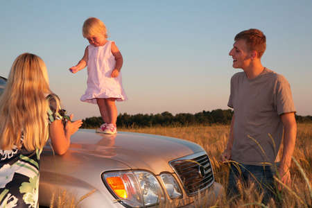 Parents and child on car cowl on wheaten field photo
