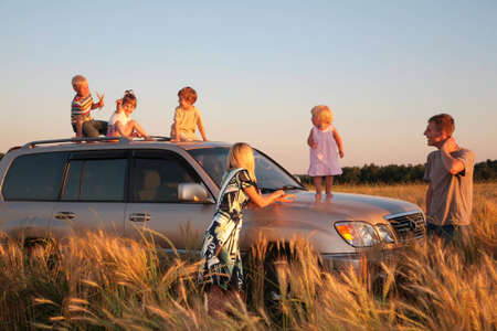 Parents and children on offroad car on wheaten field photo