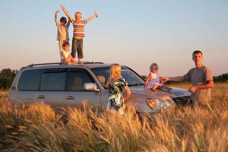 familia viaje: Los padres y los ni�os en coche en offroad wheaten campo