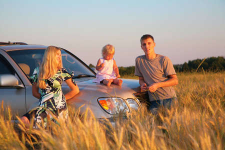 Parents and child sitting on car cowl on wheaten field photo