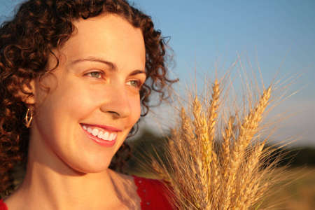 earns: Young woman face with earns on wheaten field Stock Photo