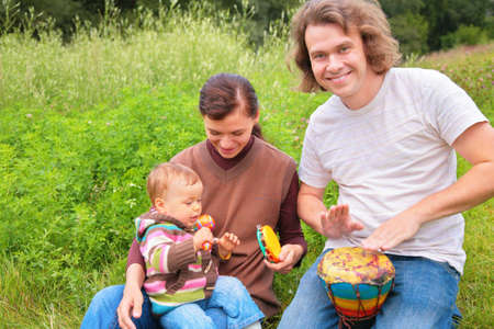 Parents and baby on nature with musical instruments   photo