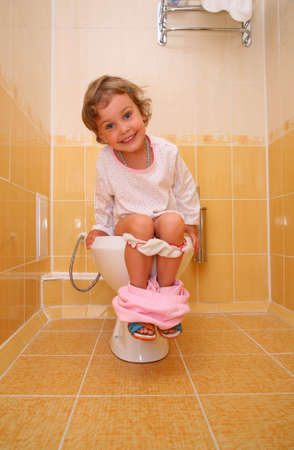 Little girl is sitting on toilet photo