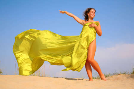 beach wrap: Young girl on sand in yellow fabric shawl Stock Photo