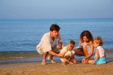 Parents play with children finding shells on sand at edge of sea photo