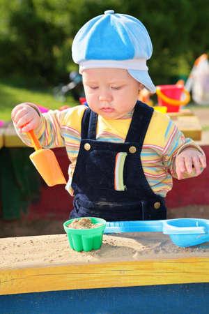 the sandbox: little boy plays in sandbox